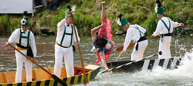 A men, dresses as a woman, falls into the water during the Fischerstechen